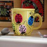 yellow coffee mug with painted ladybugs on it