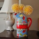 red and blue vase with crafter yellow flowers
