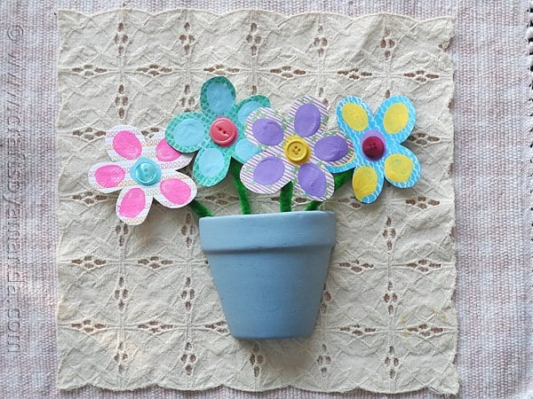 colorful scrapbook paper cut into flower shapes dotted with fingerprints