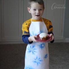 boy holding cupcake wearing sharpie snowflake apron