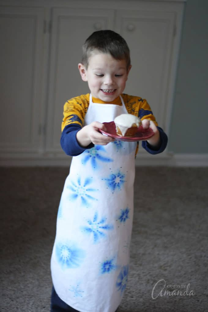 excited boy wearing apron and holding cupcake
