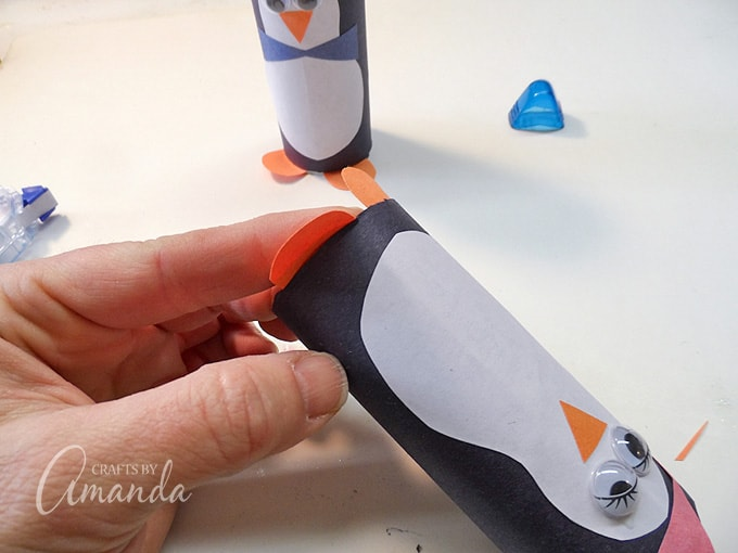 gluing feet to cardboard penguin