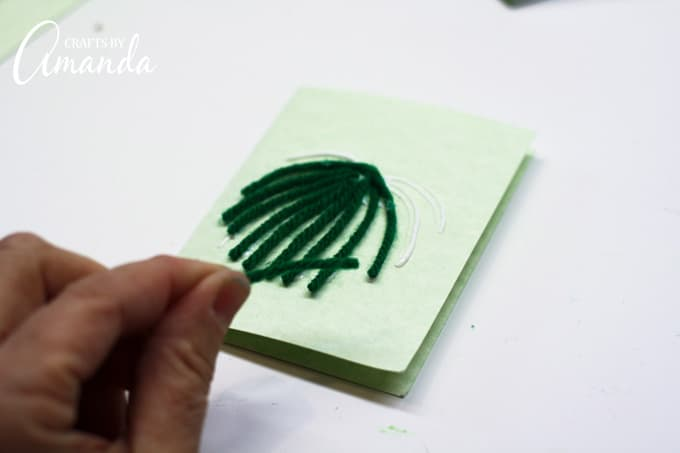 Cut yarn into pieces and place onto glue lines of your monster cards
