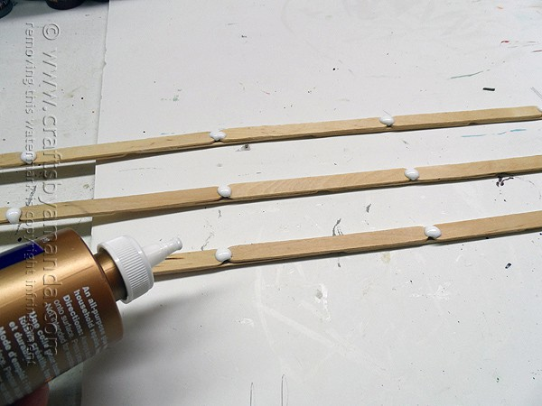 Add glue to the craft sticks where the fence posts will go