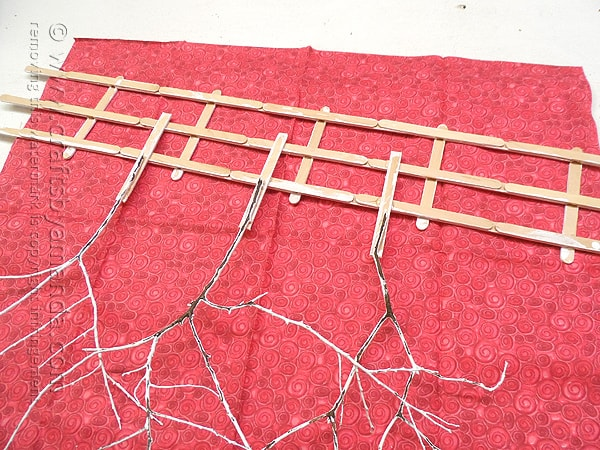 Attach the twig trees to the back of the craft stick fence