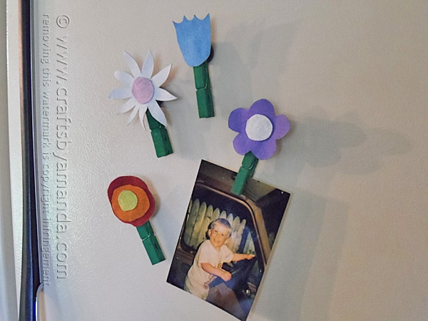 Aww what a cute way to display photos or kid's artwork on the fridge!  Flower magnets made from old denim. Genius.
