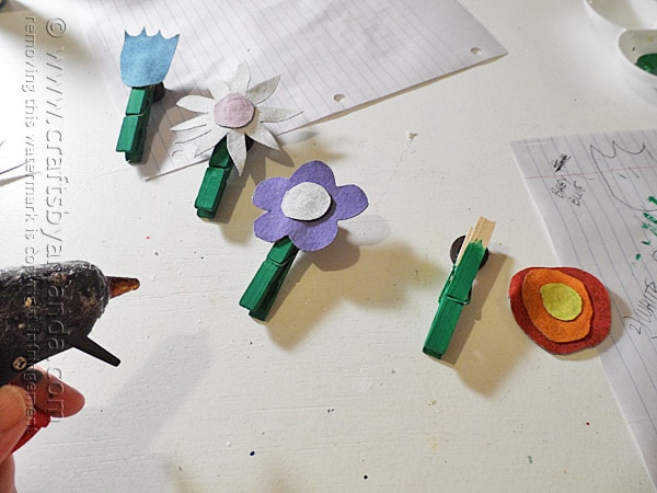 Glue the denim flowers to the clothespins