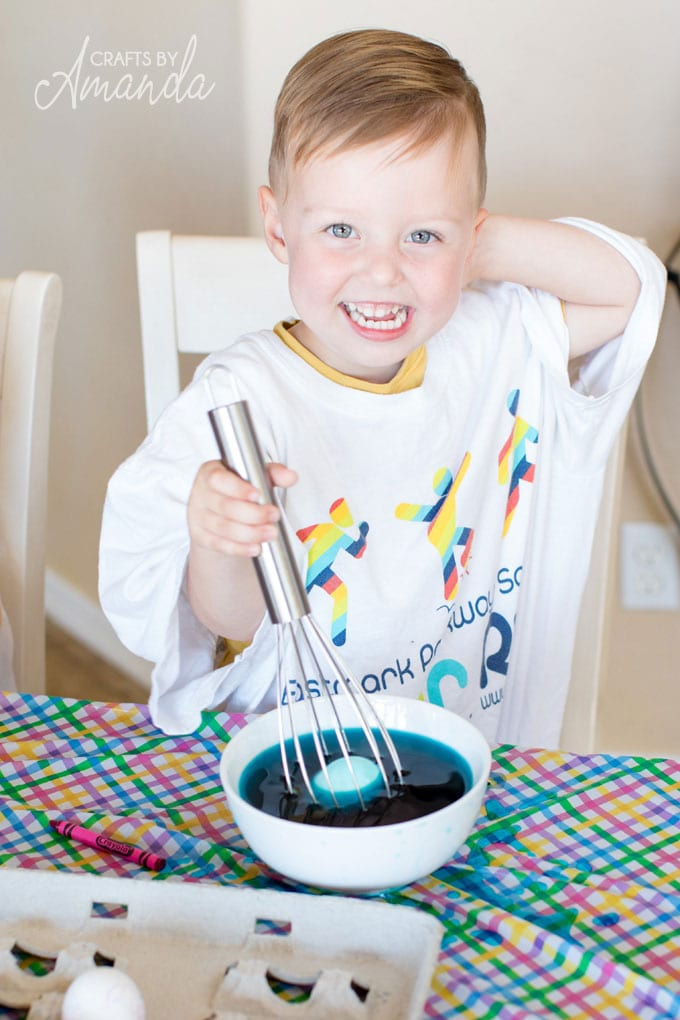 young boy dyeing easter eggs with a whisk