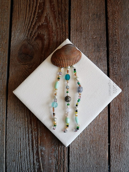 This beautiful jellyfish is made with a seashell and pretty beads, then attached to a canvas, love it!