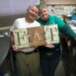 Manny and April of Manny's Snack Shack in Twin Lakes, WI with EAT Sign by Amanda Formaro @amandaformaro of Crafts by Amanda
