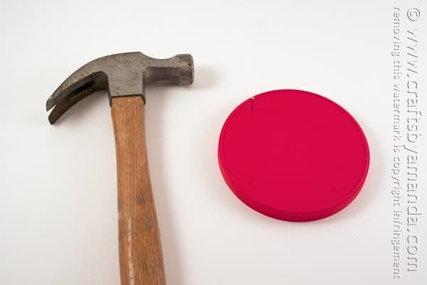 Use the hammer and nail to make four holes (like a plus sign) in the large lid. Set the lid aside.