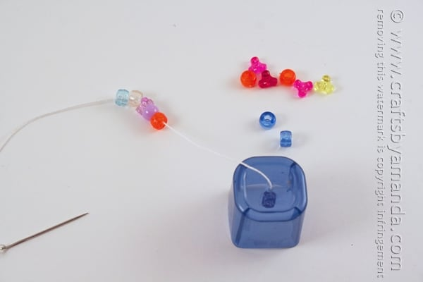 Add several beads to the string and push them to the end.