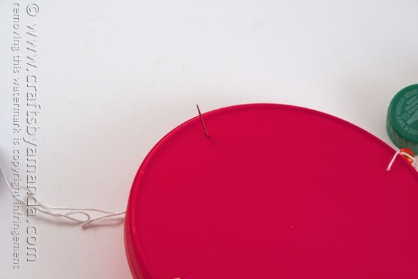 Poke the needle through one of the holes you made in the large lid in step 1.