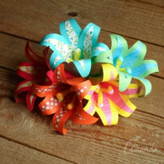 five paper flowers with a tropical theme bunched together