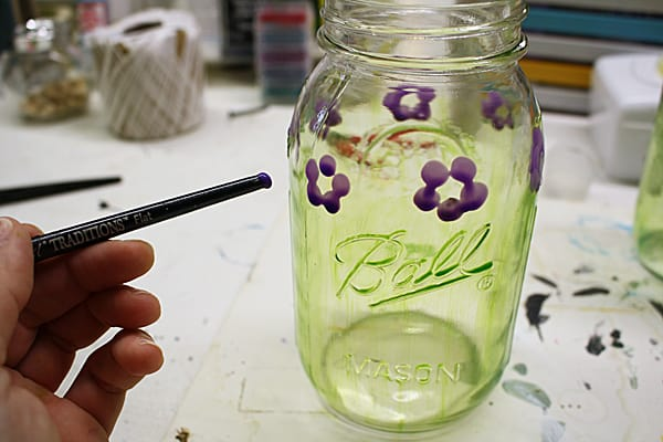 adding flowers to the mason jars