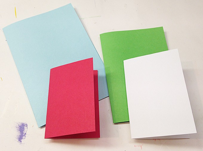 If your card stock is square, trim it so that it's a rectangle. Fold card stock in half to create the cards.