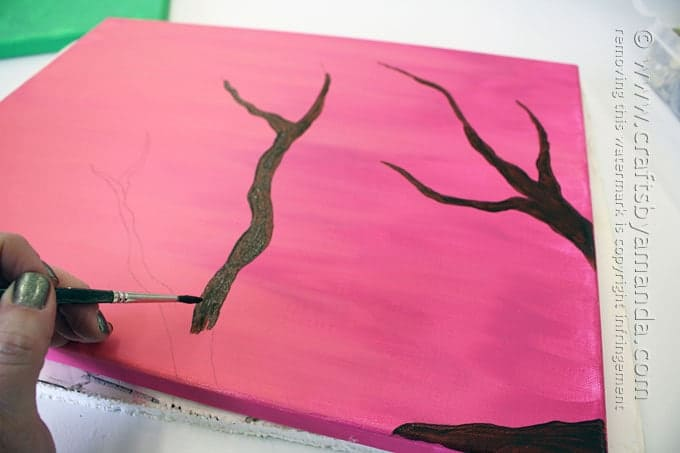 painting a tree branch on pink canvas