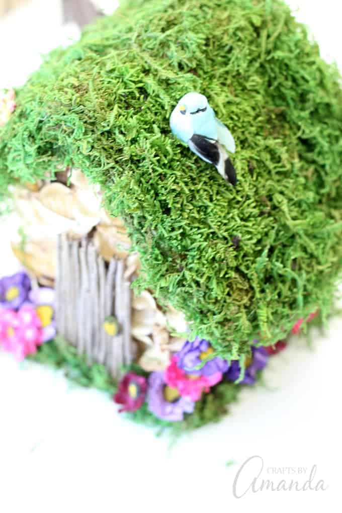 faux blue bird on top of birdhouse
