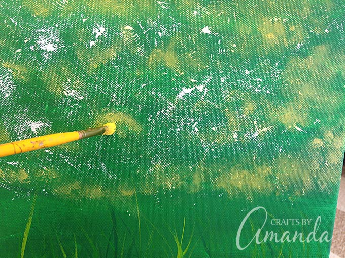 adding to the field of dandelions with a scruffy paint brush and yellow paint