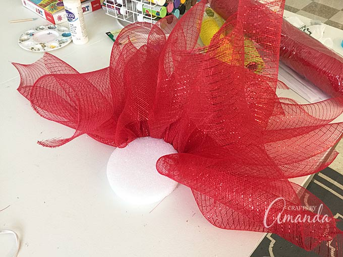 Learn how to make this beautiful deco mesh poinsettia flower - perfect for Christmas! All you need is a styrofoam disc, deco mesh and floral pins. Get the full tutorial for this pretty deco mesh flower!