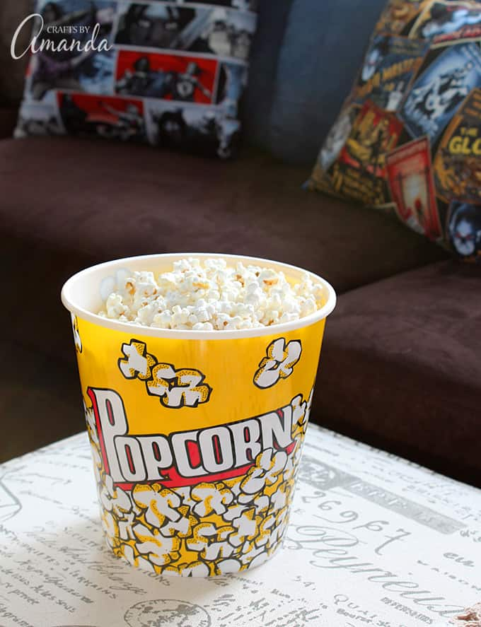 Decorate your family room with movie theater themed decor for a fun mini theater room experience! Fun movie room wall art, zombie pillows, a real popcorn maker and even candy and snacks make this room a fun place for family movie night.