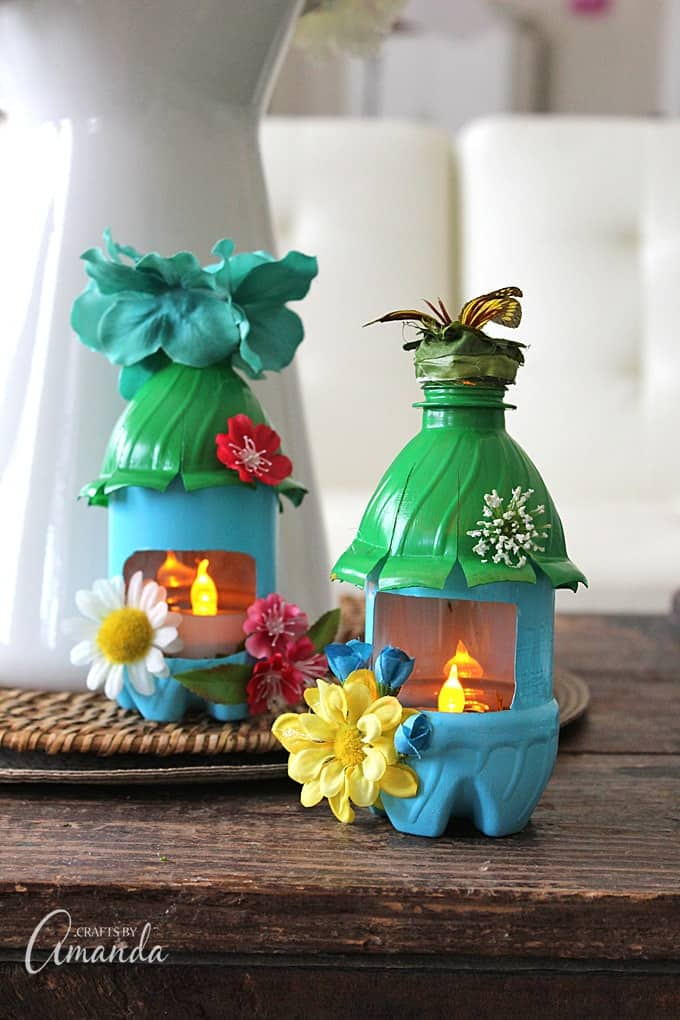 Plastic water bottles that are painted and decorated to look like fairy houses