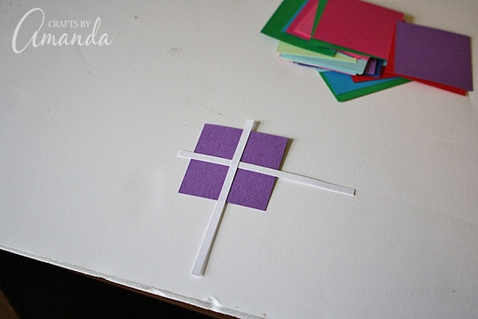 "Use a glue stick to attach white strips in a criss cross pattern to create little ""presents"" to go on your envelopes."