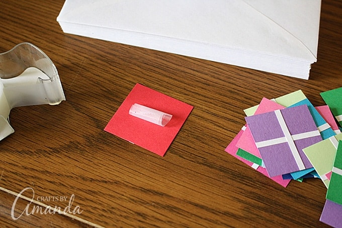 "Roll a piece of clear tape, sticky side out, and press it onto the back of the ""present""."