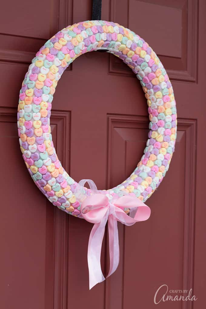 Conversation hearts turned into a wreath hanging on door