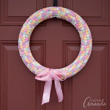 You've probably seen a variation or two of the conversation heart wreath, and I'm going to show you how to make one. It's easy and adorable!