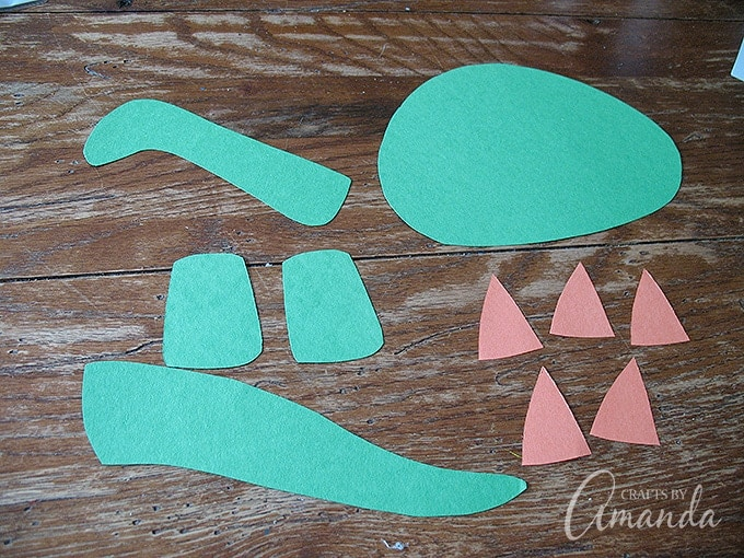 Cut out the body parts from the green construction paper and the triangle plates from the orange construction paper.