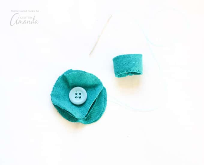 Sew the button on in the center of the stack of fabric circles and then sew the flower on the band at the seam.