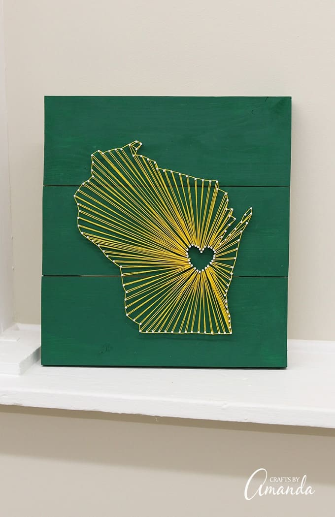 State string art makes a great gift and it's a fun craft project for adults. This one has a green and gold color scheme because the gift recipient is a Green Bay Packer fan, however stained wood and white string is a popular choice with these types of projects.