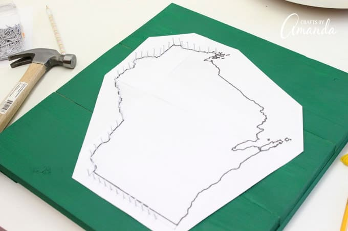 Next you will position your enlarged state print out onto your wooden board. You may want to tape the edges in a few places just to hold it still while you begin adding nails.