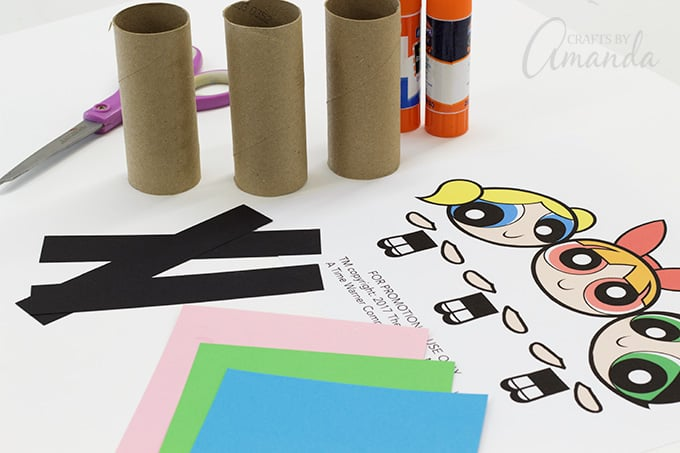 To make Cardboard Tube Powerpuff Girls you will need: 3 (4-inch) toilet paper tubes (or cut an 11-inch paper towel tube evenly into thirds), Construction paper or scrapbook paper in pink, blue, green, white and black, Glue stick, Scissors or cutting board, Black marker or crayon