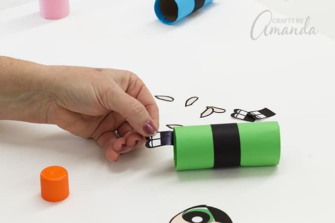 Use glue stick to attach the legs to the inside of each tube.
