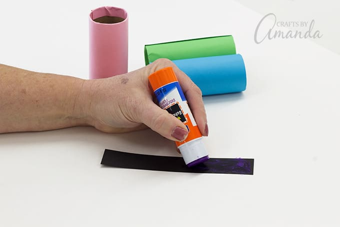 Cut 3 strips of black paper, each measuring 1-inch x 6-inches. Glue a black strip around the center of each tube.