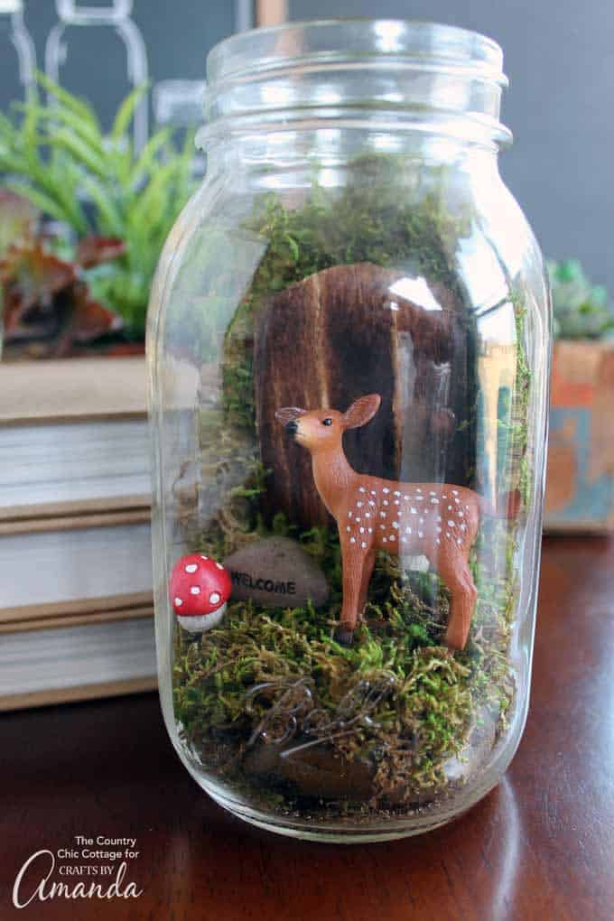 Add in your fairy door and any miniatures using hot glue to your Fairy Garden Mason Jar Terrarium.
