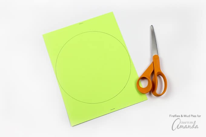 Hold the stacked pieces of card stock together, then cut a slit from one side of the circle all the way up to the center. Slide the slits into each other to create the illusion of 1 flat circle.
