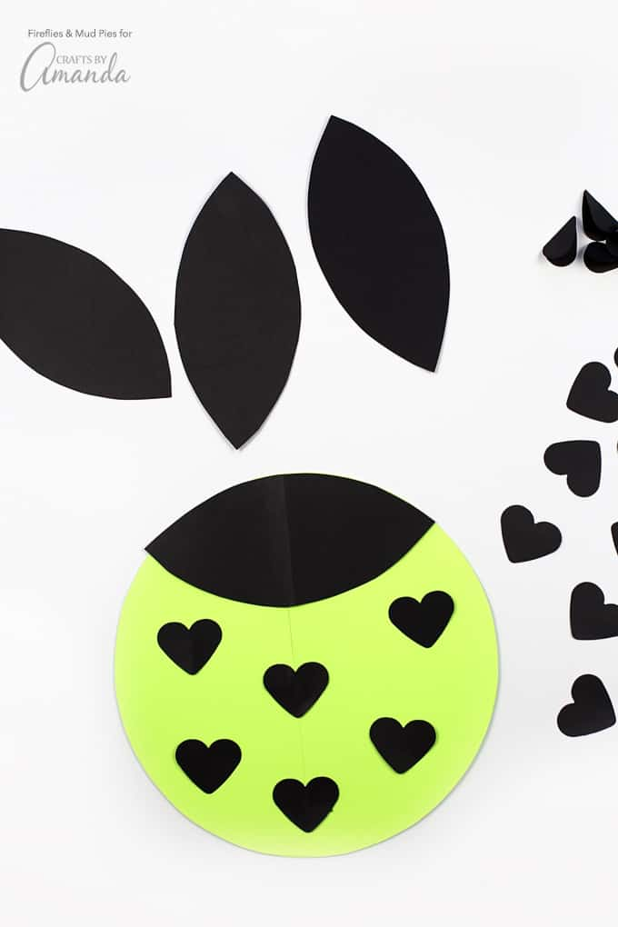 "Staple 2 pieces of black card stock together, then trace the shape you just cut out twice. You will need 4 of those rounded ""leaf"" shapes to be the lovebug's face. Fold the shapes in half…then grab your double-sided tape or Glue Dots."