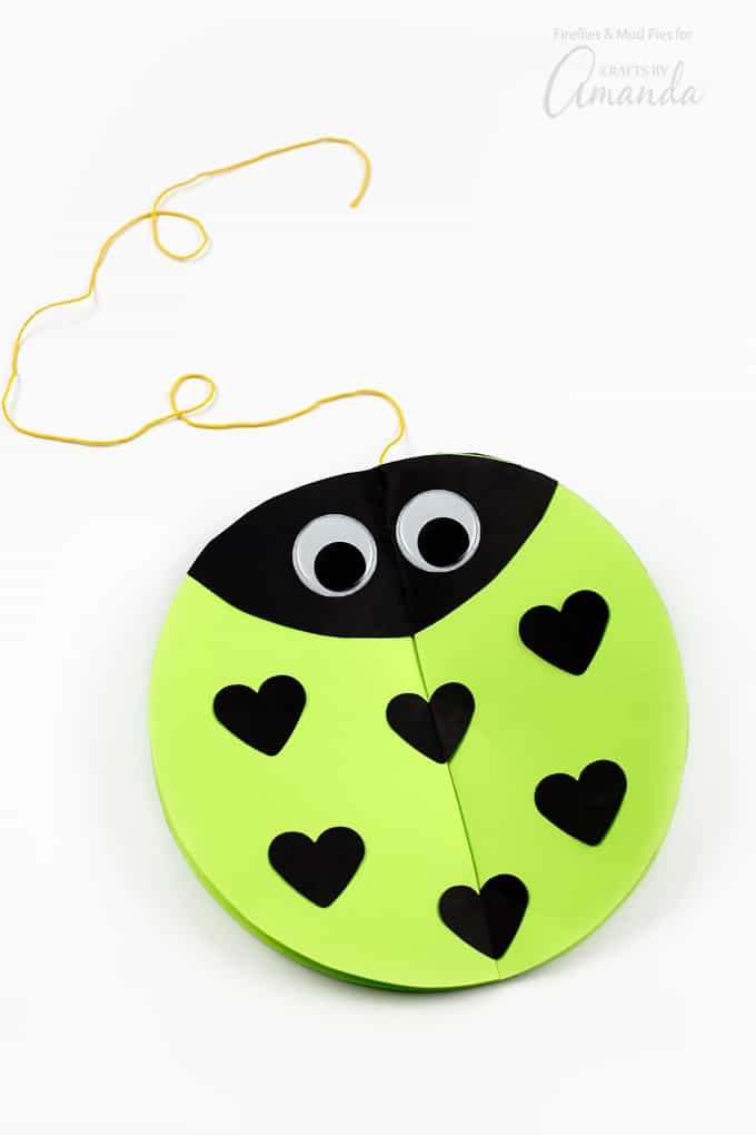 "With the circle laying flat, tape down one of the black ""leaf"" shapes for the love bug's face. Tape 2 hearts down the center, and 2 on each side of the circle. These center hearts and the love bug's face will prevent your little lovebug from sliding apart when you hang it up."