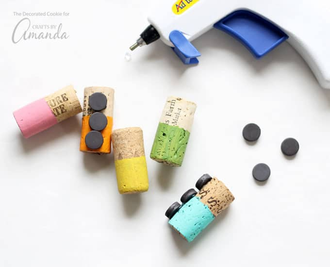 Use the hot glue gun to glue two to three magnets on the side of the cork. Let set well.