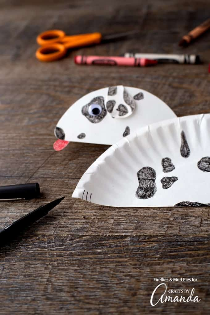 """As a finishing touch, invite kids to use a black pen to draw """"paws"""" at the end of the large paper plate arch to finish off the paper plate dalmatian."""