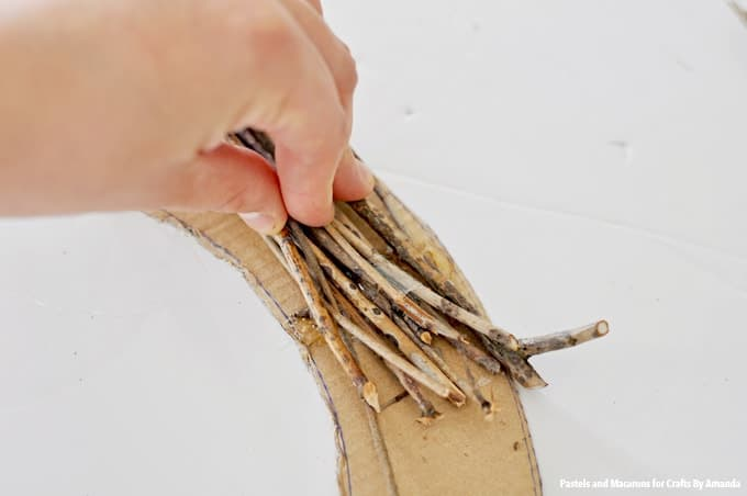 Use hot glue to add twigs to wreath form