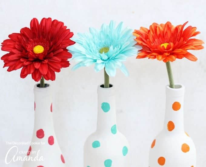 Red, blue, and orange polka dot painted wine bottles as vases