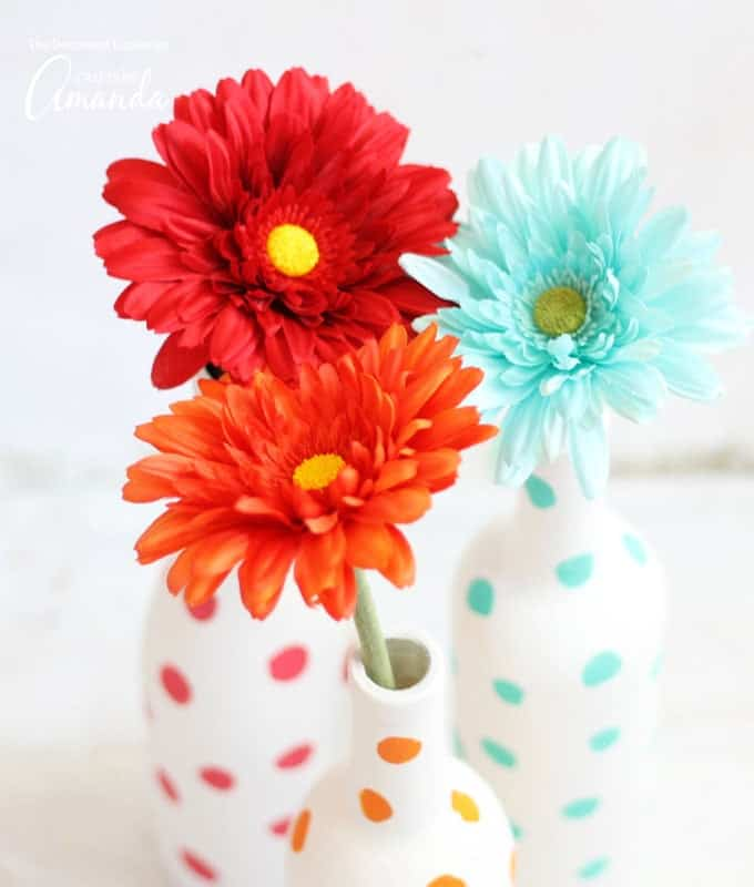 bright colored flowers in polka dot painted wine bottles