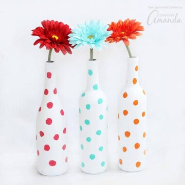 These Polka Dot Wine Bottle Vases are the perfect wine bottle craft! Pair with brightly-colored flowers to add a bit of cheer to any room in your house.