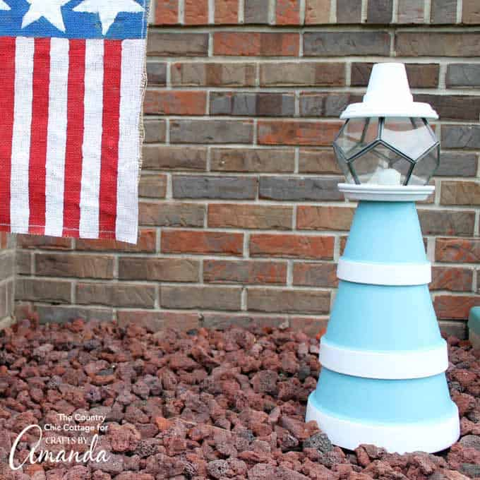nautical themed clay pot lighthouse sitting in a bed of rocks