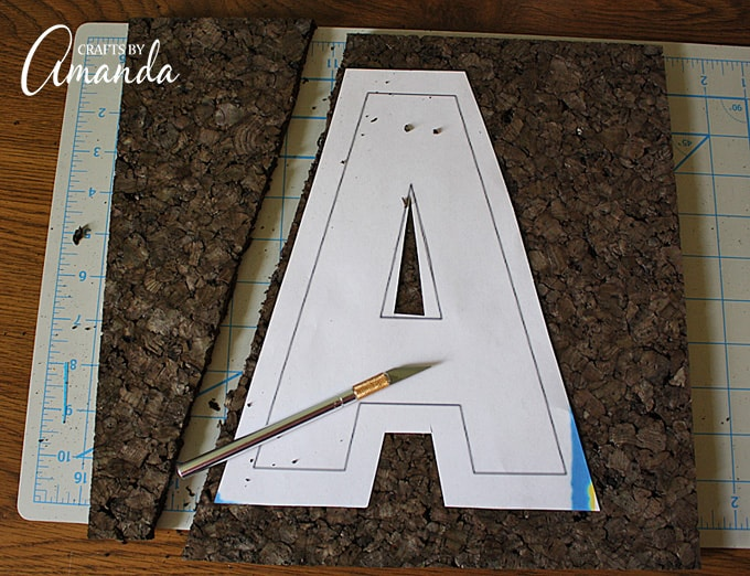 Place cork tile on top of the cutting mat. Hold the letter in place on top of the cork (you can add thumbtacks to hold it in place) and use the craft knife to cut through the cork in the shape of the letter.