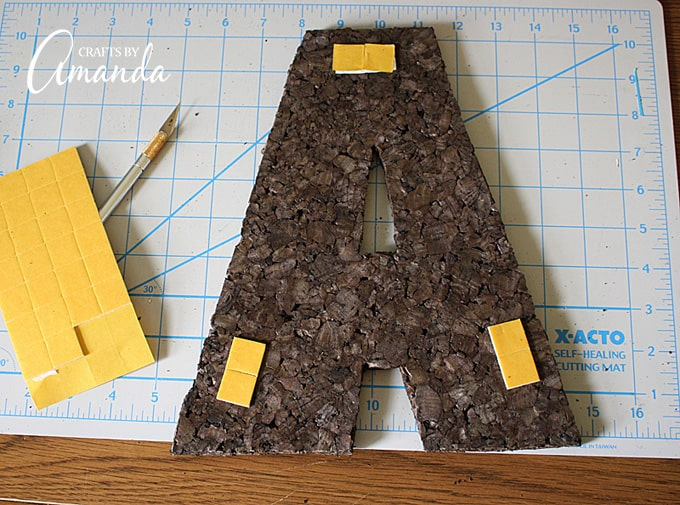 Cork tiles usually comes with self adhesive wall mounts. Attach a few to the back and hang it on the wall.
